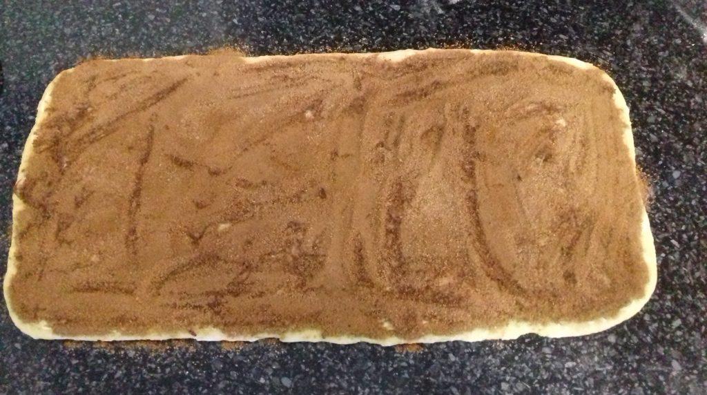 testo dlya cinnabon smazannoe maslom i posypannoe koricej s saharom